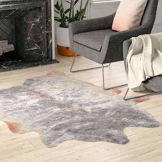 A Grey and brown Novelty style rug, sitting next to a chair providing an added level of comfort.
