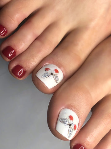 Beautiful pedicure made with nail decals and sliders
