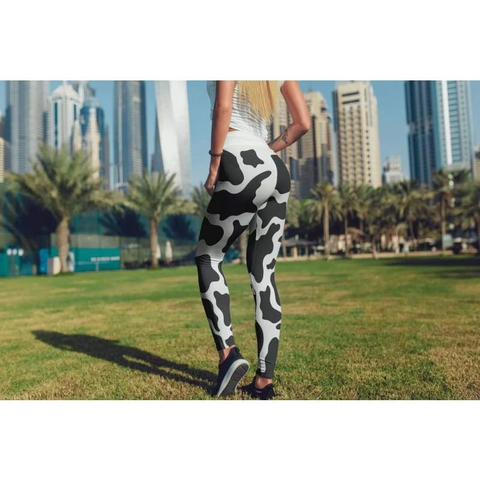 Sporting a pair of vibrant cow print leggings while walking in the park