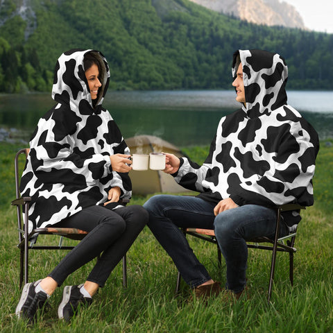 man and women driking coffee in their cow print snug rug hoodies
