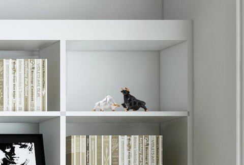 a pair of black and white miniature bull displayed in a cabinet shelf