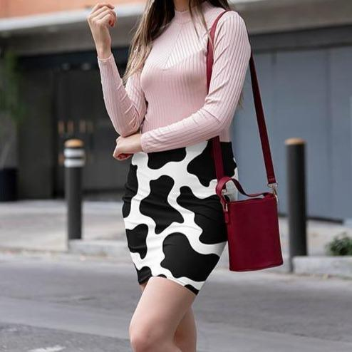 young woman wearing a Cow Print Mini Skirt matched with a pink top and red shoulder bag | Cow Loco