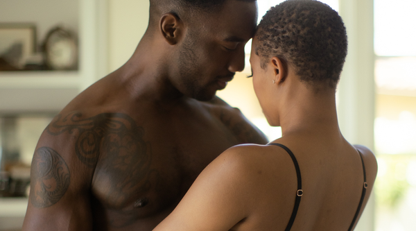 Closeup of a shirtless black male and a young black female close together