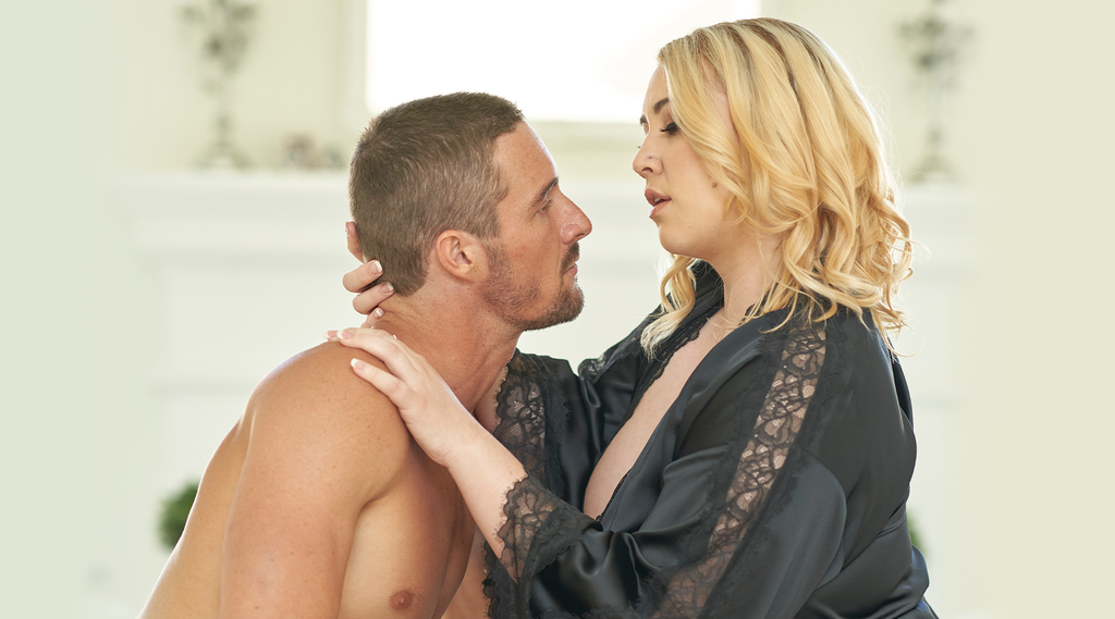 Side facing attractive young man and attractive young blond women looking at one another passionately
