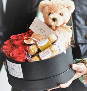 red roses in a round box, round flower box, round bloom box, red roses, flowers in black box, round flower arrangement, flowers and chocolate, teddy bear and roses, roses with chocolates