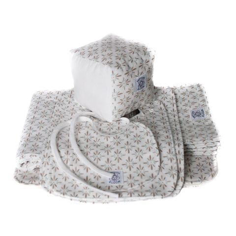 So Soft Organic Cotton Baby Accessories Package showing the contents of the package including a receiving blanket, diaper change pad, 2 burp pads, 3 sizes of bibs and a play/learning block