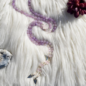 Mala prayer bead necklace made with amethyst and rose quartz crystals, pearls, and moon charm