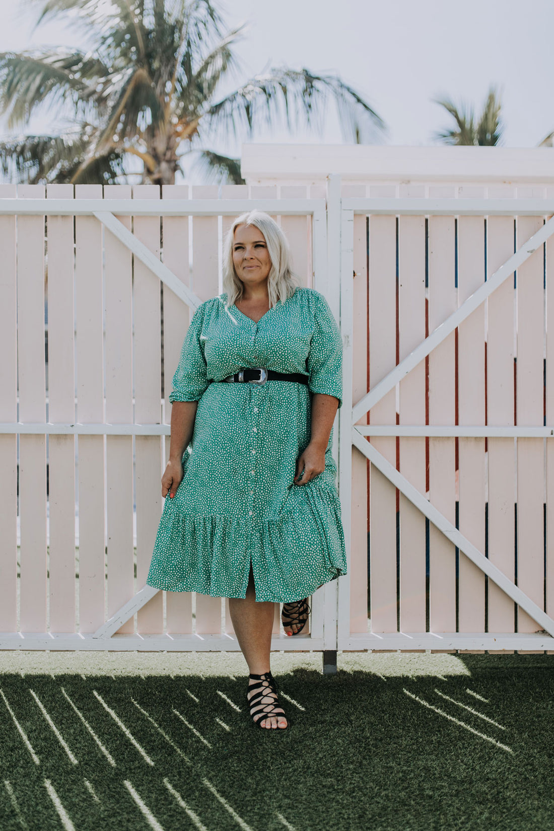curvy woman with blonde hair wearing beautiful emerald green alila midi joy dress from ada + lou smiling while standing in front a light pink fence in the sunshine