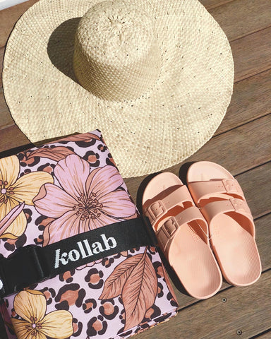 straw hat, towel and plastic shoes in a flat lay from Pineapple traders