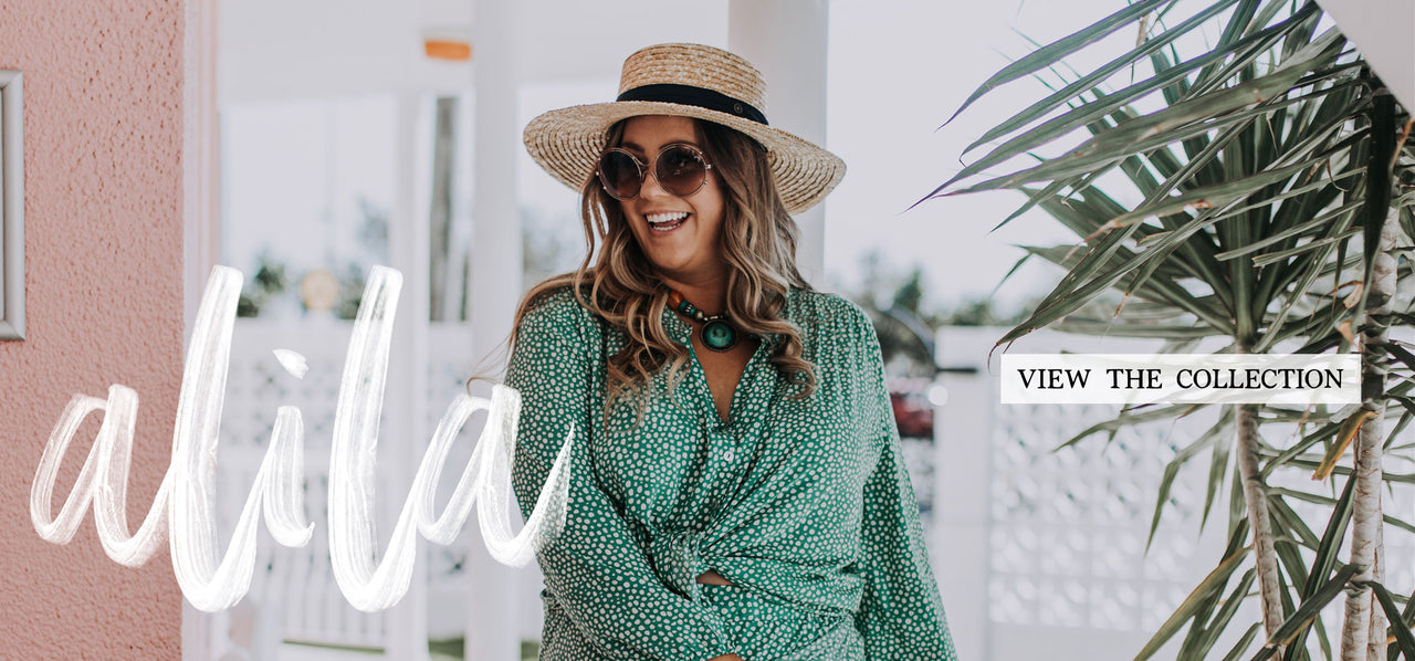 Joyful blonde curvy woman wearing emerald Alila blouse from ada + lou and emerald all willow skirt , straw hat and sunglasses at retro hotel