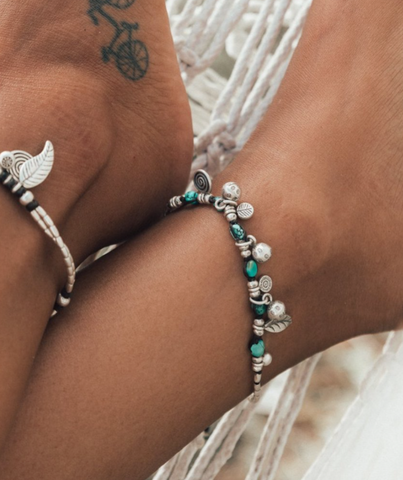 close up of ankles wearing silver and turquoise anklets