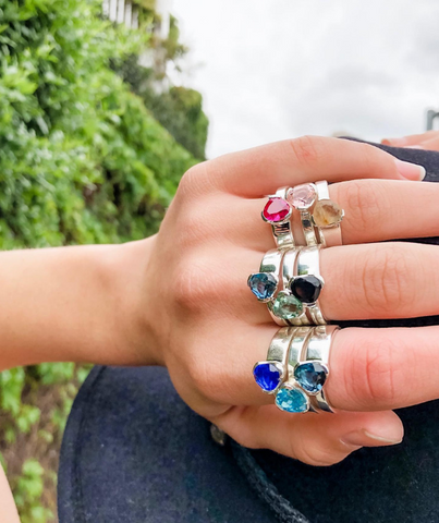 closeup of hand with stack of silver and gemstone rings on all fingers