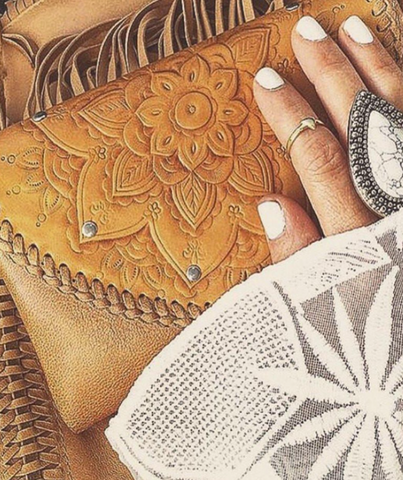 closeup of hand wearing silver boho ring resting on mahiya leather embossed leather purse