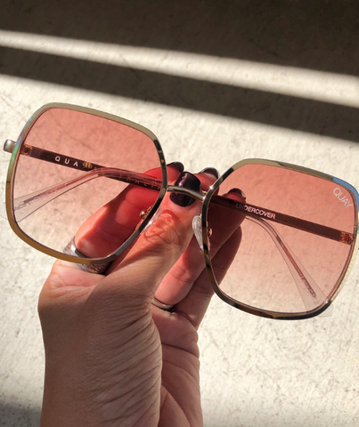 close up of hand holding retro glasses from quay sunglasses australia