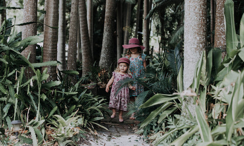 two young girls frolicking in a tropical garden while wearing ada + lou