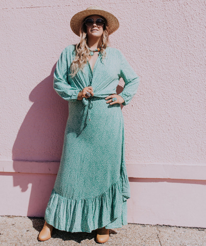 blonde model leans against pink wall while wearing ada + lou alila willow skirt and ophelia blouse in emerald.