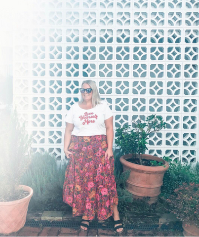 Curvy blonde model, Chantelle Ellem wears bohemian maxi skirt and statement tee while standing in front of lesser block wall