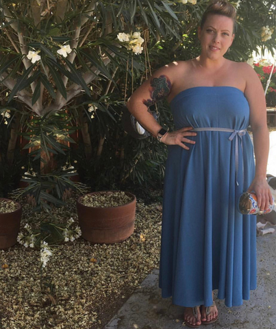 Holly Zigga wears a blue skirt as a dress while standing in a garden