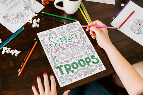 """coloring page that reads """"support our troops"""" partially colored in pink and green, sitting on a tabletop that is also holding colored pencils, popcorn, a cup of coffee and a variety of coloring pages, with a woman's hands holding a pink colored pencil"""