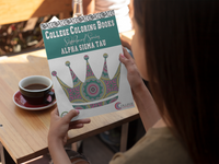 woman sitting at table with a cup of coffee holding an Alpha Sigma Tau coloring book