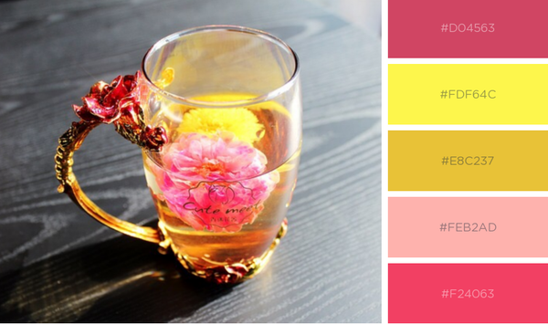 Glass cup of tea with pink and yellow flowers in it