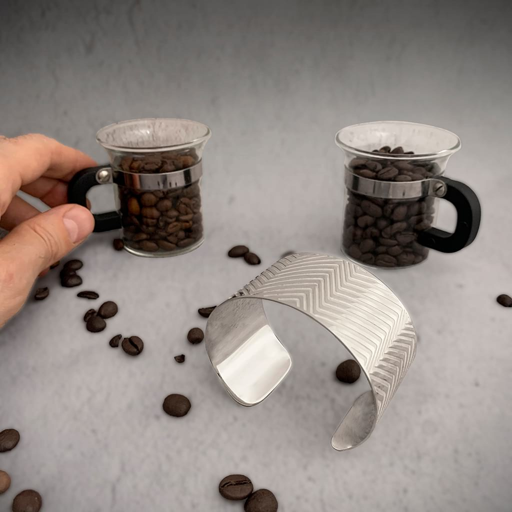 two coffee cups filled with coffee beans and a silver wide bracelet on a surface