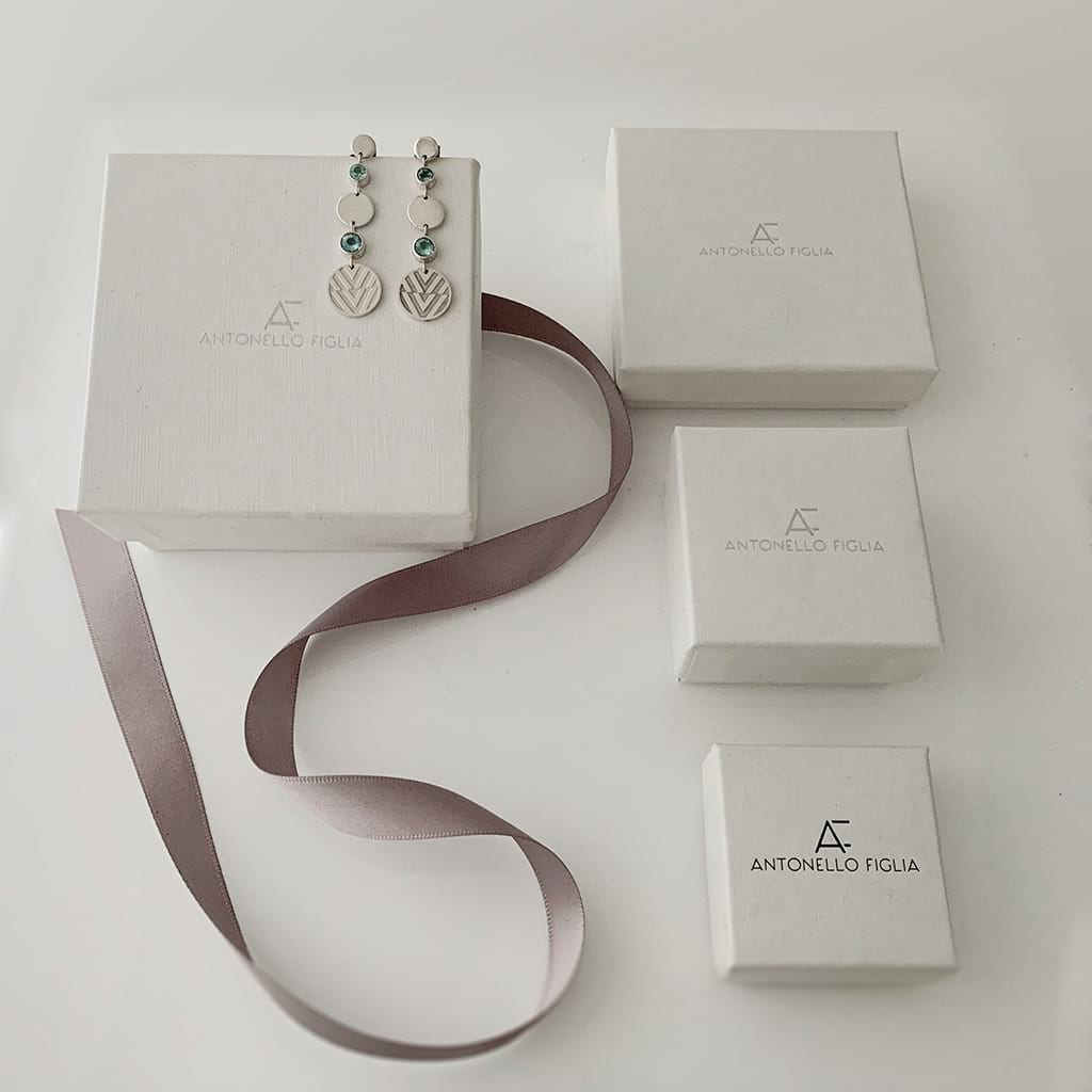 drop earrings laying around jewellery boxes and ribbon