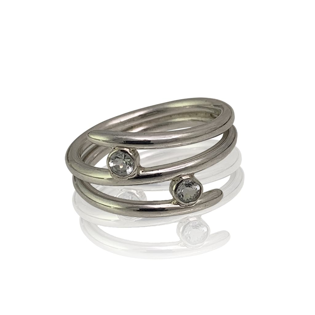 silver ring with two aquamarine gemstones lying flat on a white background