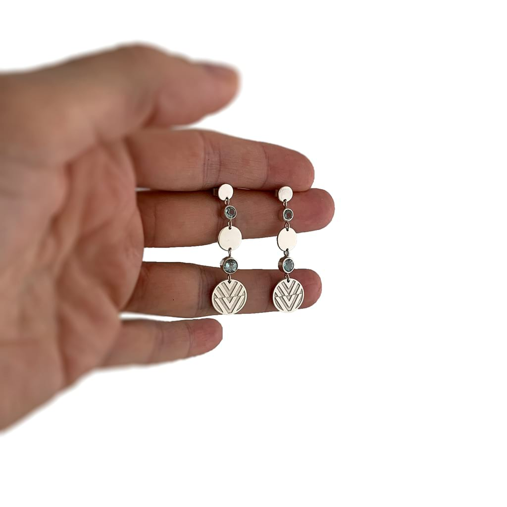 Hand holding a long pair of earrings
