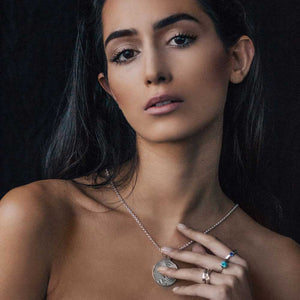 model holding a silver pendant in her hand
