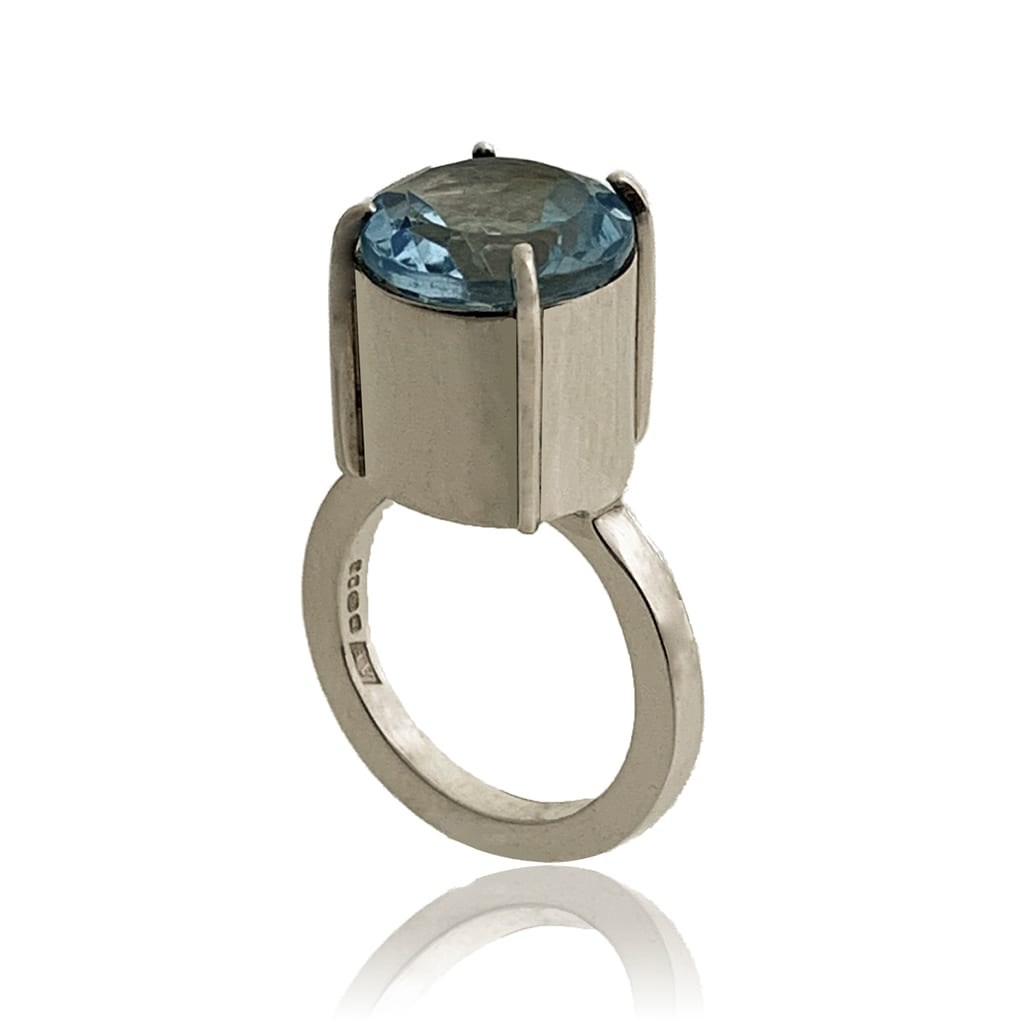 Silver ring with faceted Topaz gemstone on a white abckground