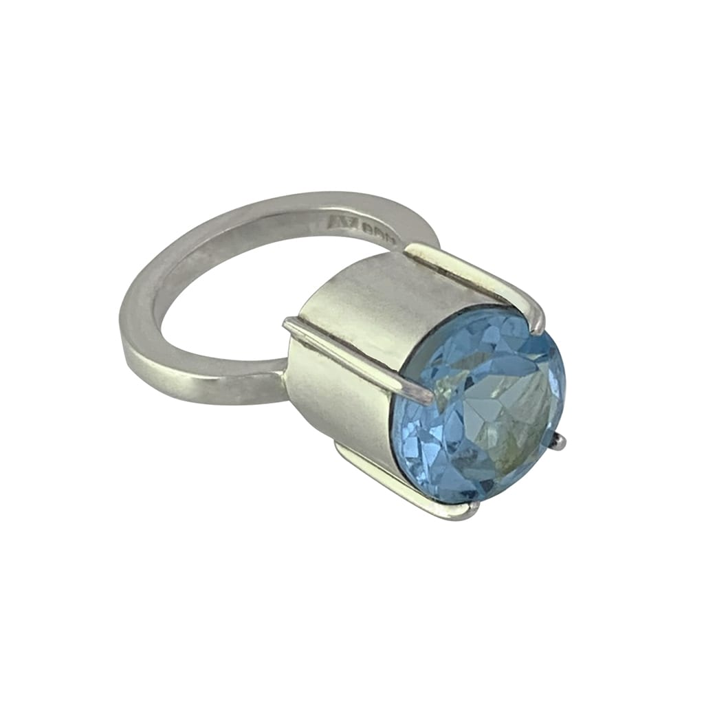 Silver Ring Set with 11mm Blue Topaz Gemstone Lying Flat on a White Background