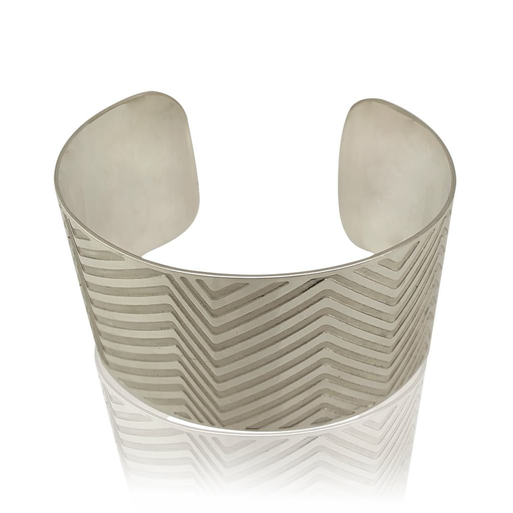 Wide Silver Oval Cuff With Etched Lines Laying Flat on a White Background