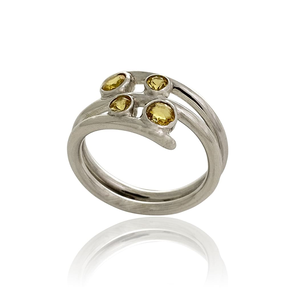 A women silver ring with yellow sapphires sideview on a white background