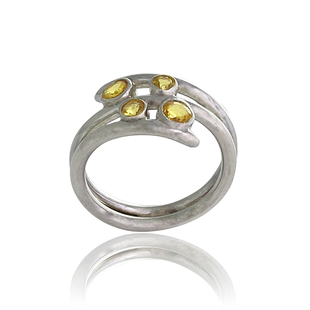 A women silver ring with four round yellow sapphires detail on a white background