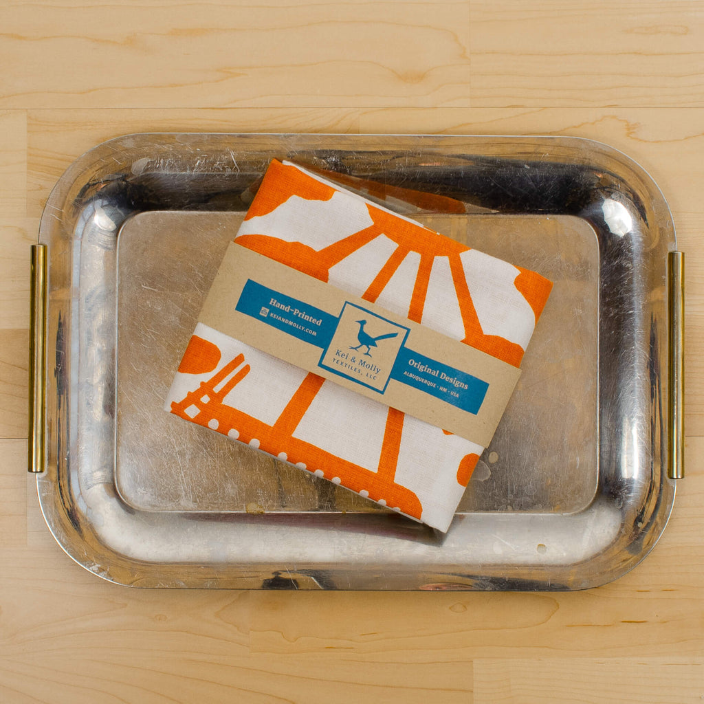 Kei & Molly Linen/Cotton Tea Towel with Adobe House Design in Orange Folded on Tray