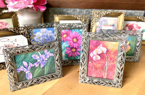 a tabletop filled with small floral prints in metal frames