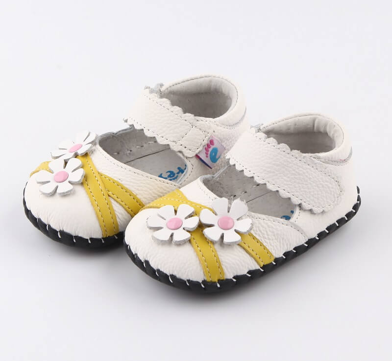 White leather baby girl shoes yellow stripes and daisy flowers side view