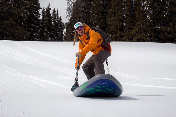 Woman Snow SUP Paddleboard Snowsled Mountains