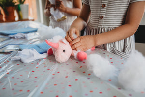 stuffing a pink unicorn plush pet
