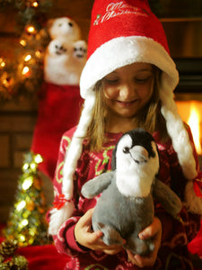 Girl at Christmas with Penguin plush stuffy