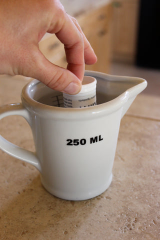 Place balm tube top down in cup of hot water (approximately 3-5 minutes)