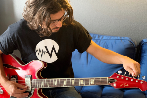 Man wearing cool T-shirt and tuning guitar