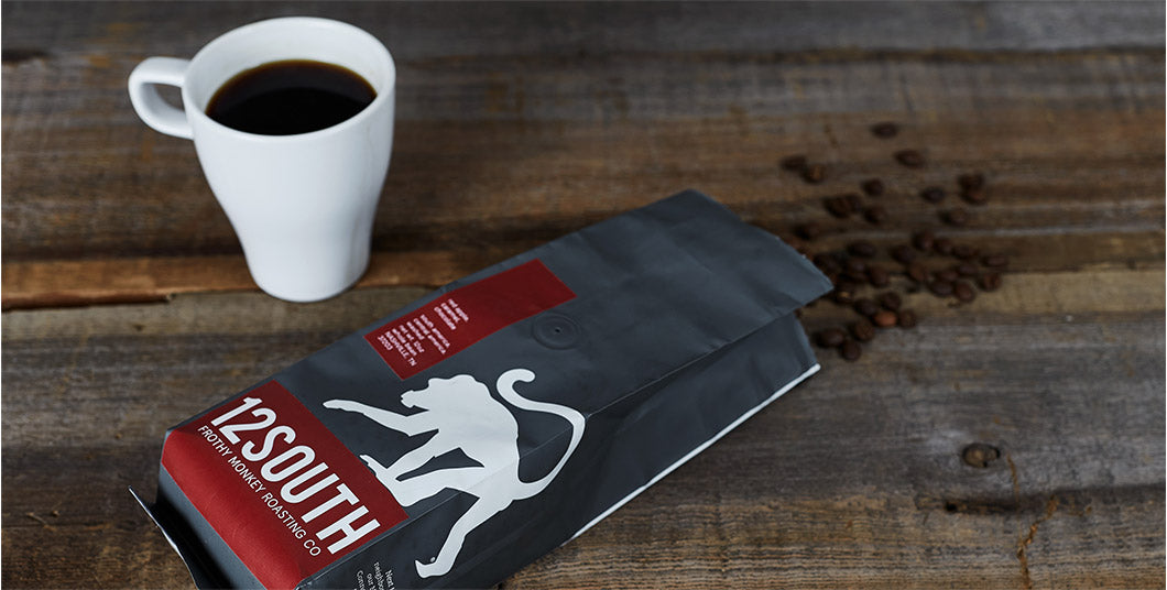 Frothy Monkey cup of coffee and coffee grinds packaging