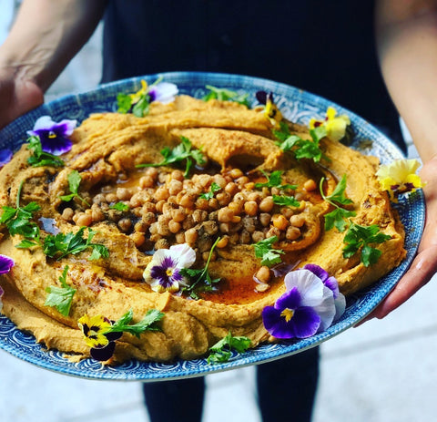 A large platter of hummus is held by two hands.