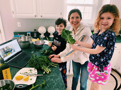 A mom cooking with her kids while watching a laptop