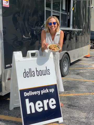 "Julie is standing in front of the mobile kitchen, holding a bowl, over the sign that reads ""della bowls: pick up deliveries here."""