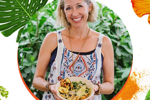 Chef Julie Frans wears a blue apron and smiles holding a colorful della bowl layered with grains, vegetables, nuts and sauce.