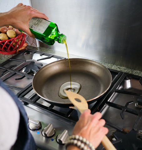 Pouring olive oil in a non-stick pan in preparation for cooking