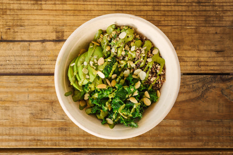 the green bowl at della bowls is layered with quinoa, lentils, mixed greens, sesame broccoli, avocado, basil-walnut sauce, and toasted almonds